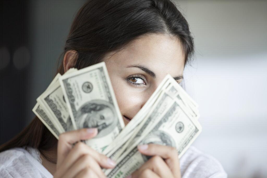 Woman peeking behind hundred dollar bills