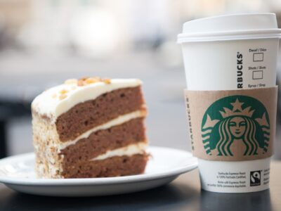 Paris , France-September 27, 2017: A tall Starbucks coffee in starbucks coffee shop with cake. Starbucks is the world's largest coffee house with over 20,000 stores in 61 countries.