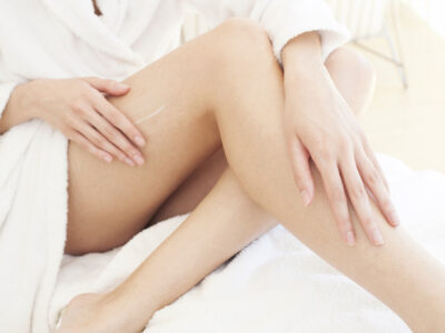 MODEL RELEASED. Young woman applying cream to leg.