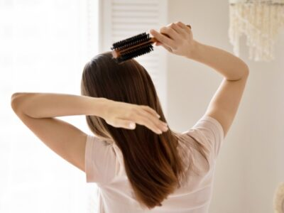 Rear view young woman combing healthy long straight hair with wooden brush at home, beautiful girl enjoying morning routine after awakening at home, doing hairstyle, beauty treatment